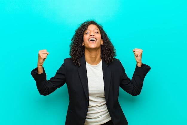 Junge schwarze frau, die glücklich, überrascht und stolz sich fühlt, erfolg mit einem großen lächeln gegen blaue wand schreit und feiert