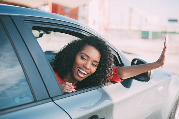 Junge schwarze frau, die im autolächeln sitzt