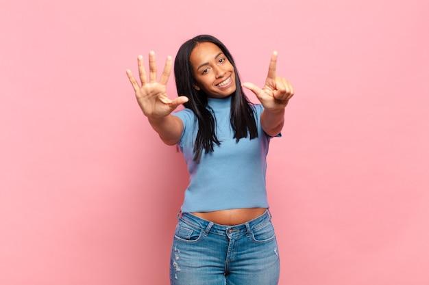 Junge schwarze frau, die lächelt und freundlich aussieht, die nummer sieben oder siebt mit der hand nach vorne zeigt und herunterzählt