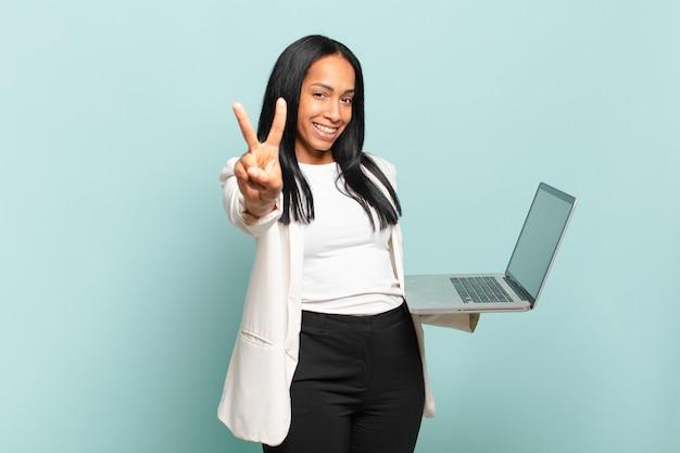 Junge schwarze frau, die lächelt und freundlich aussieht, die nummer zwei oder die zweite mit der hand nach vorne zeigt, herunterzählen. laptop-konzept