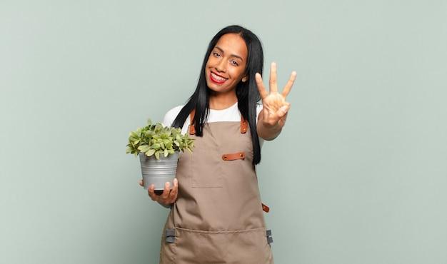 Junge schwarze frau, die lächelt und freundlich aussieht und nummer drei oder dritte mit der hand nach vorne zeigt, herunterzählen. gärtnerkonzept