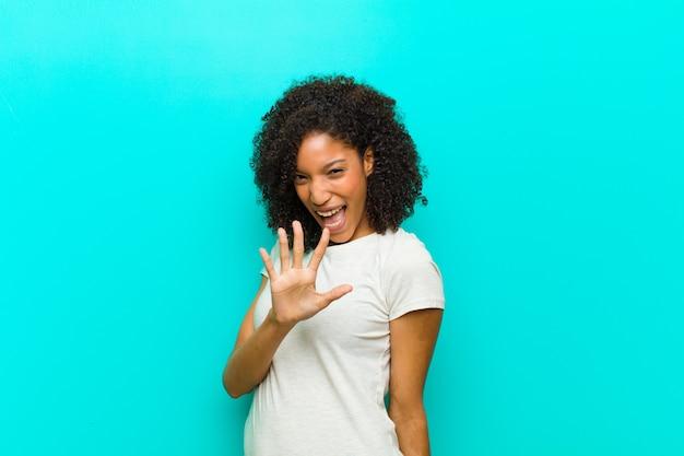 Junge schwarze frau, die lächelt und freundlich schaut, nummer fünf oder fünften mit der hand nach vorne zeigend, über blaue wand herunterzählend