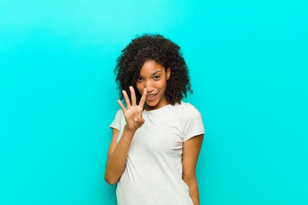 Junge schwarze frau, die lächelt und freundlich schaut, nummer vier oder vierten mit der hand nach vorne zeigend, gegen blaue wand herunterzählend