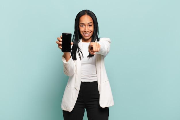 Junge schwarze frau, die mit einem zufriedenen, selbstbewussten, freundlichen lächeln auf die kamera zeigt und sie wählt. smartphone-konzept