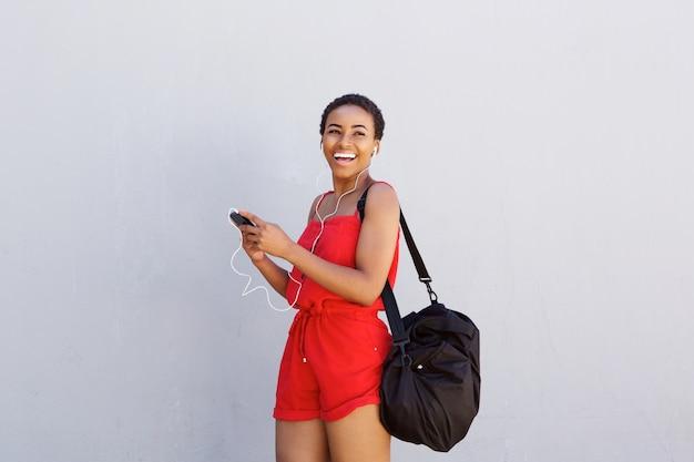 Junge schwarze frau, die mit mobiltelefon und kopfhörern lächelt