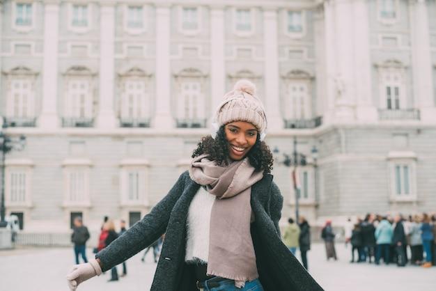 Junge schwarze frau, die musik hört und am handy nahe dem königlichen palast im winter tanzt