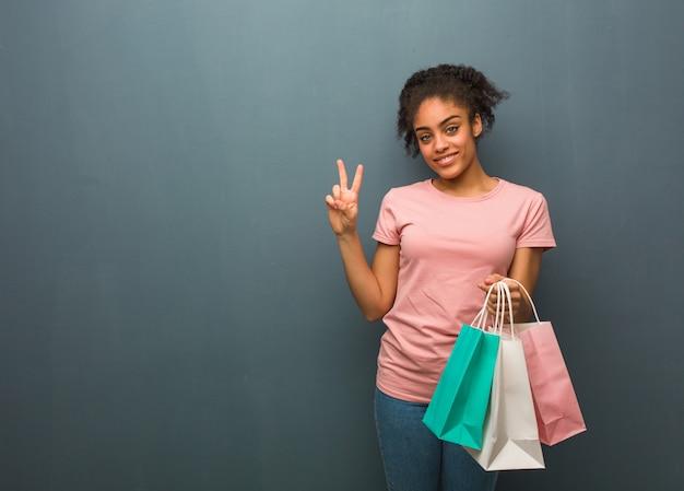 Junge schwarze frau, die nummer zwei zeigt. sie hält eine einkaufstüte.