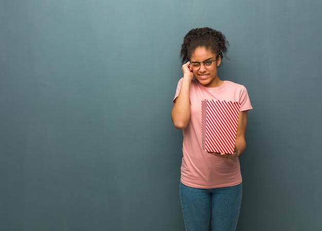 Junge schwarze frau, die ohren mit händen bedeckt. sie hält einen popcorn-eimer in der hand.
