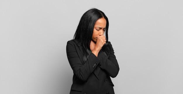 Junge schwarze frau, die sich mit halsschmerzen und grippesymptomen krank fühlt und mit bedecktem mund hustet. geschäftskonzept