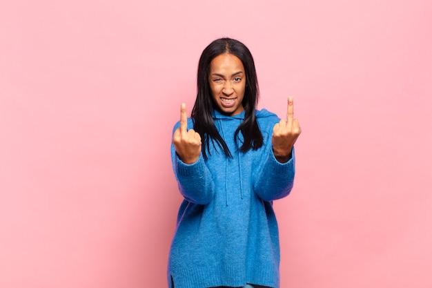 Junge schwarze frau, die sich provokativ, aggressiv und obszön fühlt, den mittelfinger zeigt, mit einer rebellischen haltung