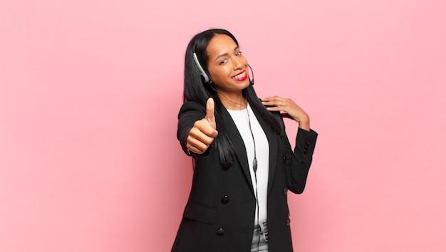 Junge schwarze frau, die sich stolz, sorglos, selbstbewusst und glücklich fühlt und positiv mit daumen nach oben lächelt. telefonmarketing-konzept