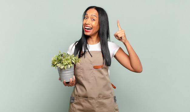 Junge schwarze frau, die sich wie ein glückliches und aufgeregtes genie fühlt, nachdem sie eine idee verwirklicht hat, fröhlich den finger hebt, heureka!. gärtnerkonzept