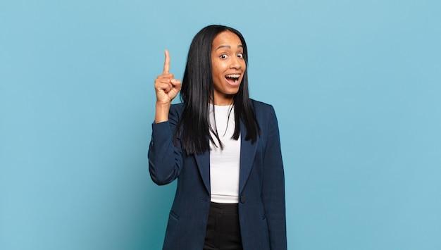 Junge schwarze frau, die sich wie ein glückliches und aufgeregtes genie fühlt, nachdem sie eine idee verwirklicht hat, fröhlich den finger hebt, heureka!. geschäftskonzept
