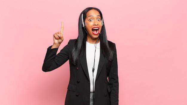 Junge schwarze frau, die sich wie ein glückliches und aufgeregtes genie fühlt, nachdem sie eine idee verwirklicht hat, fröhlich den finger hebt, heureka!. telefonmarketing-konzept