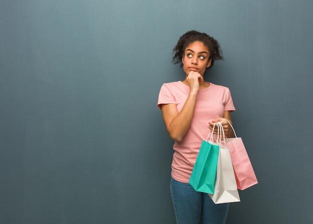 Junge schwarze frau, die über eine idee nachdenkt. sie hält eine einkaufstasche in der hand.