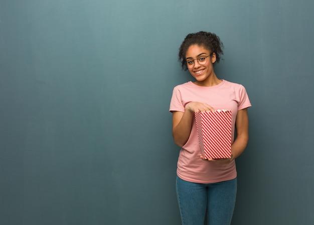 Junge schwarze frau freundlich mit einem großen lächeln. sie hält einen popcorn-eimer in der hand.