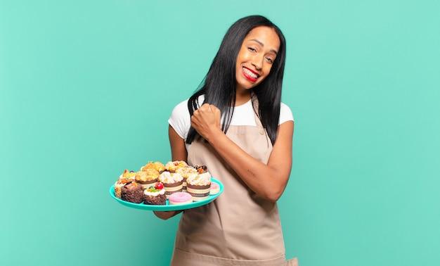 Junge schwarze frau fühlt sich glücklich, positiv und erfolgreich, motiviert, wenn sie sich einer herausforderung stellt oder gute ergebnisse feiert. bäckerkochkonzept