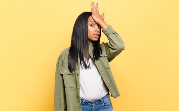 Junge schwarze frau hebt die handfläche zur stirn und denkt, oops, nachdem sie einen dummen fehler gemacht oder sich daran erinnert hat, sich dumm zu fühlen