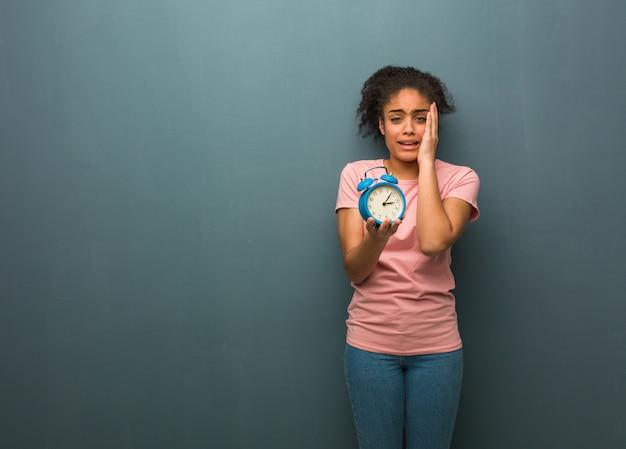 Junge schwarze frau hoffnungslos und traurig. sie hält einen wecker.
