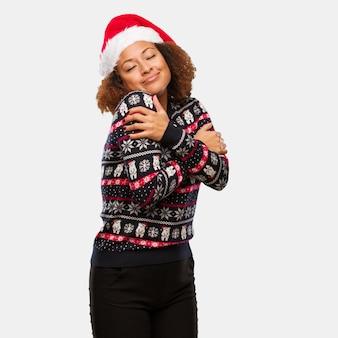 Junge schwarze frau in einer modischen weihnachtsstrickjacke mit dem druck, der eine umarmung gibt