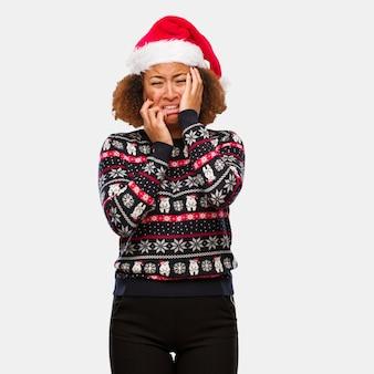Junge schwarze frau in einer modischen weihnachtsstrickjacke mit dem druck verzweifelt und traurig