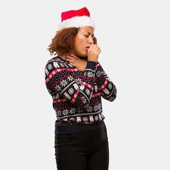 Junge schwarze frau in einer modischen weihnachtsstrickjacke mit dem druckhusten, krankem bedingtem virus oder einer infektion