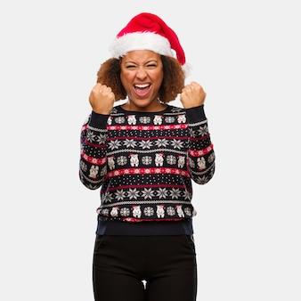 Junge schwarze frau in einer modischen weihnachtsstrickjacke mit druck sehr verärgert und aggressiv schreiend