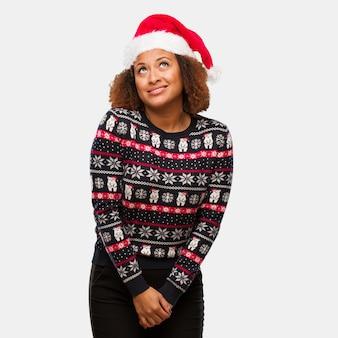 Junge schwarze frau in einer modischen weihnachtsstrickjacke mit druck träumend vom erreichen von zielen und von zwecken