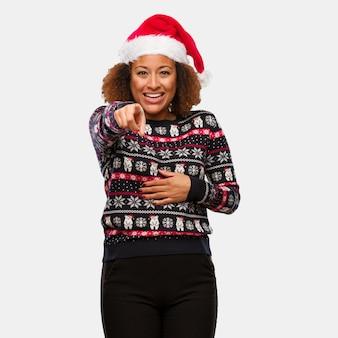 Junge schwarze frau in einer modischen weihnachtsstrickjacke mit druck träumt vom erreichen von zielen und von zwecken