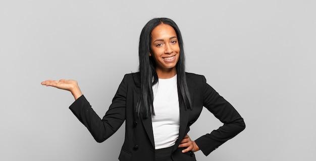 Junge schwarze frau lächelt, fühlt sich selbstbewusst, erfolgreich und glücklich und zeigt konzept oder idee auf dem kopierraum auf der seite. geschäftskonzept