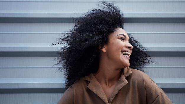 Junge schwarze frau mit afro-haaren, die lachen und genießen