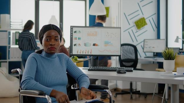 Junge schwarze frau mit behinderungen, invalide, behinderte, gelähmte behinderte, die frustriert in die kamera schaut, traurig im rollstuhl im büroraum sitzt und mit dem team an einem finanzprojekt arbeitet
