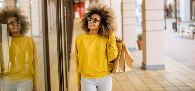 Junge schwarze frau mit dem lockigen haar beim einkaufen