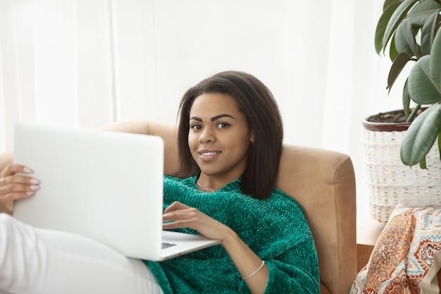 Junge schwarze frau mit laptop-computer, sitzend im hellen wohnzimmer.