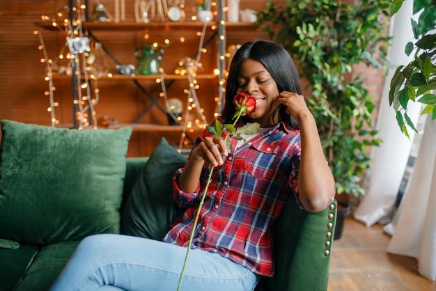 Junge schwarze frau mit roter rose, die auf sofa sitzt, romantisches treffen zu hause. glückliche afroamerikanische weibliche person auf der couch im wohnzimmer