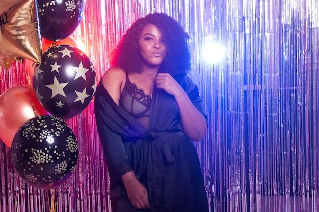 Junge schwarze frau sieht glücklich aus, während sie zeit im nachtclub verbringt. geburtstagsfeier und nachtleben konzept.