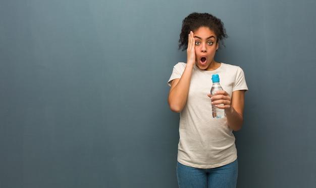 Junge schwarze frau überrascht und entsetzt. sie hält eine wasserflasche.