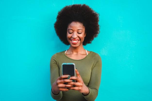 Junge schwarze frau unter verwendung des intelligenten handys - afrikanisches mädchen, das unter verwendung der web-app auf dem handy lacht und lächelt - weibliches lebensstil- und technologiekonzept - fokus auf gesicht