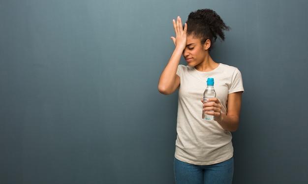 Junge schwarze frau vergesslich, etwas zu realisieren. sie hält eine wasserflasche.