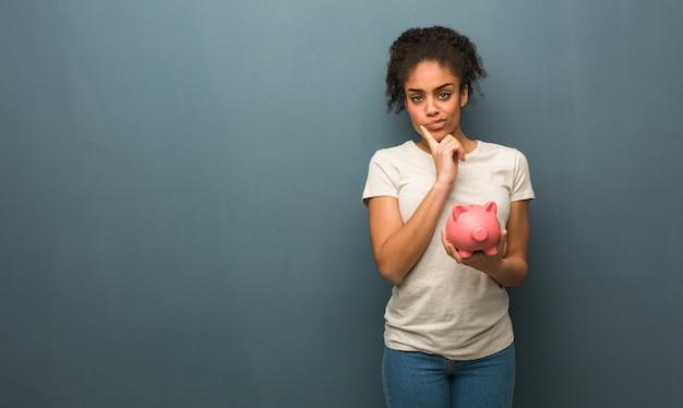 Junge schwarze frau zweifelnd und verwirrt. sie hält ein sparschwein.