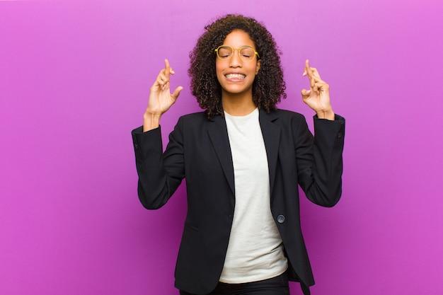 Junge schwarze geschäftsfrau, die besorgt beide finger lächelt und kreuzt