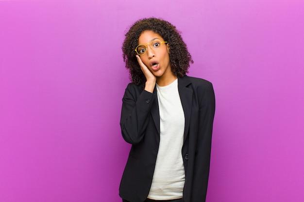 Junge schwarze geschäftsfrau, die entsetztem und erstauntem holdinggesicht sich fühlt, um mit weit offenem mund im unglauben zu übergeben