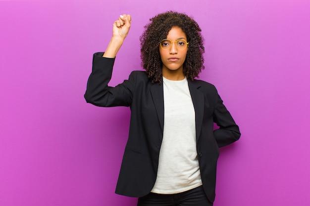 Junge schwarze geschäftsfrau, die ernst, stark und rebellisch sich fühlt, faust oben anhebt, für revolution protestiert oder kämpft