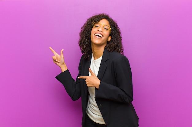 Junge schwarze geschäftsfrau, die froh und überrascht sich fühlt, mit einem entsetzten ausdruck lächelt und auf die seite zeigt
