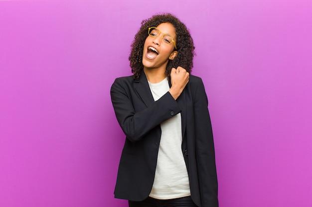 Junge schwarze geschäftsfrau, die glücklich, positiv und erfolgreich sich fühlt, motiviert, wenn sie einer herausforderung gegenübersteht oder gute ergebnisse feiert