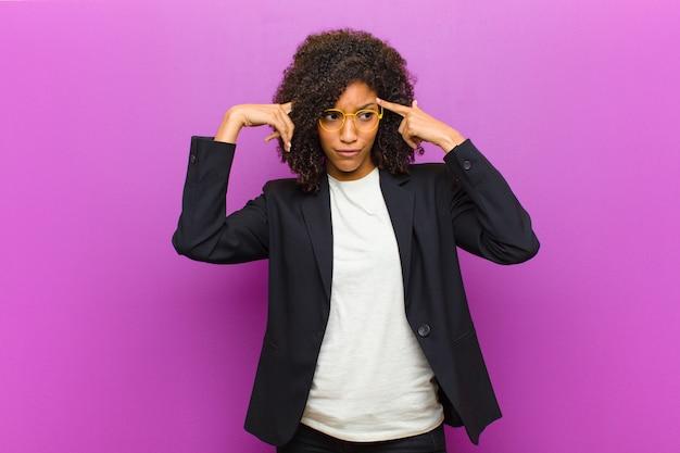 Junge schwarze geschäftsfrau, die konzentriert schaut und denkt