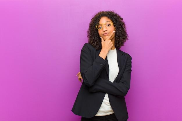 Junge schwarze geschäftsfrau, die, mit einem arm gekreuzt und der hand auf dem kinn, gewichtwahlen ernst, durchdacht und misstrauisch schaut