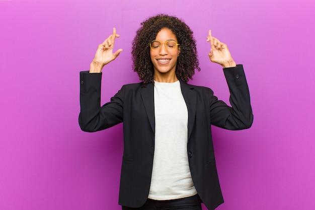 Junge schwarze geschäftsfrau, die nervös und hoffnungsvoll sich fühlt, finger kreuzt, für gutes glück betet und hofft