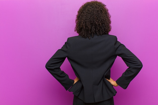Junge schwarze geschäftsfrau, die verwirrt oder voll oder die zweifel und fragen, wundernd, mit den händen auf hüften, hintere ansicht glaubt