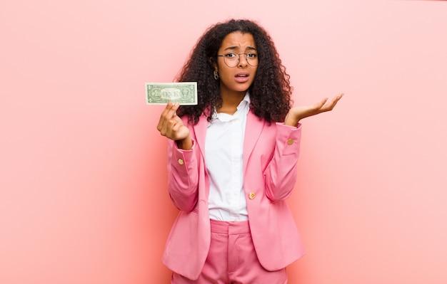 Junge schwarze hübsche frau mit dollarbanknoten gegen rosa wandhintergrund
